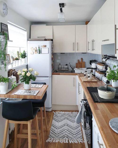 Cocina pequeña en madera, blancos y negros con plantas verdes