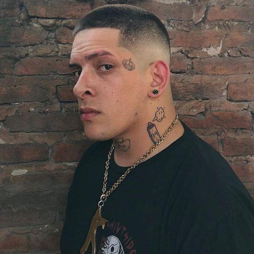 Muchacho con el pelo muy corto y tatuajes