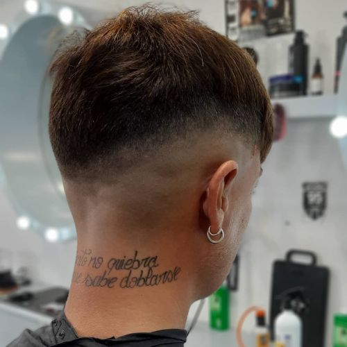 Chico con pelo corto y frase tatuada